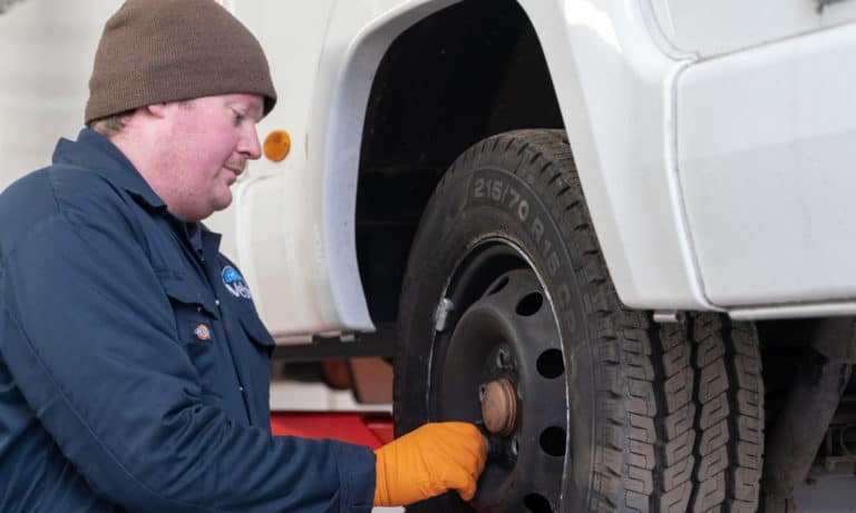 A member of the service team checking tires on a motorhome.