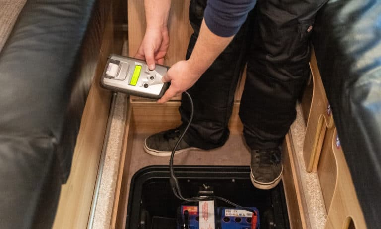 A service team testing the electrics inside of a motorhome.