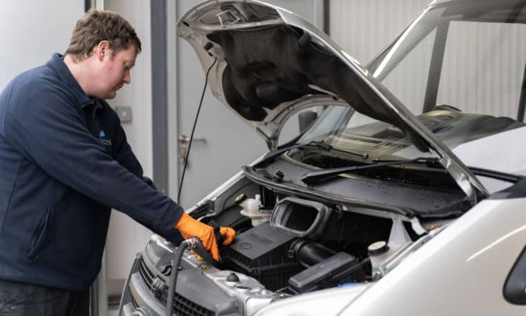 Service team testing an engine battery on a motorhome.