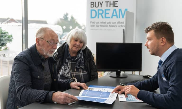 Sales staff discussing financial options with a couple at Webbs Motor Caravans.