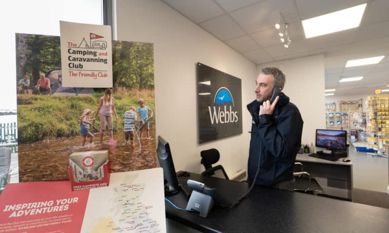 A Webbs member of staff on the phone next to the Camping and Caravanning Club sign.