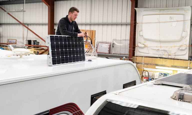 Service team reparing a caravan's solar panel in the Webbs' caravan service centre.