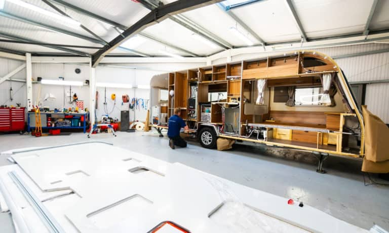 Side-view of a caravan's interior and the service team conducting a habitation inspection in the Webbs Caravans' service centre.