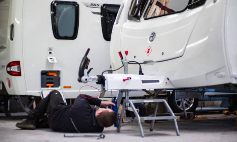 A Webbs Caravans' staff member installing a fitted mover to a caravan in the service centre.