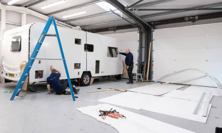 Service team reinstalling a caravan's side panel in the Webbs service centre.