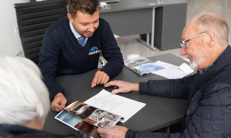 Webbs Sales staff and customer looking through a caravan brochure.