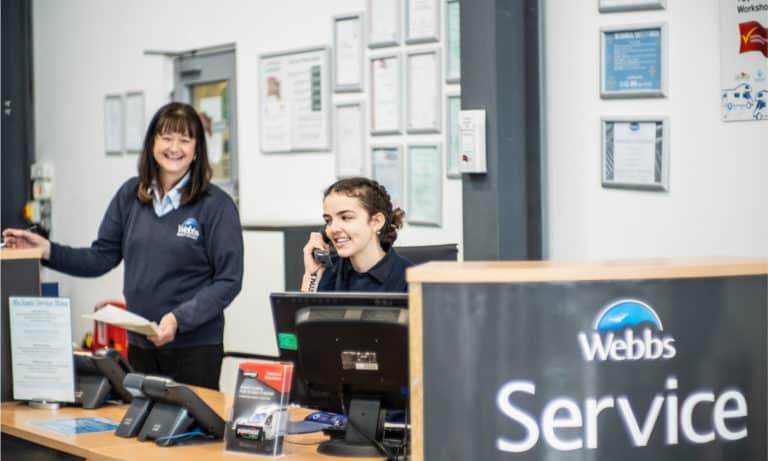 Staff members working behind the Webbs Motor Caravans' service desk.