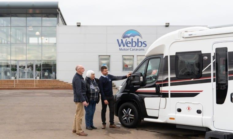 Sales staff and customers in the Webbs Motor Caravans' forecourt viewing a pre-owned motorhome.