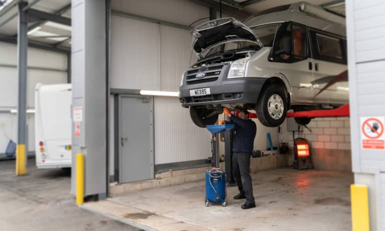 A member of the service team inspecting an undercarriage at the Webbs Motor Caravans' service centre.